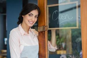 portret van serveerster staande bij de ingang foto