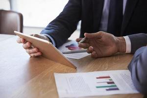 sluit omhoog van zakenlieden gebruikend digitale tablet in vergadering foto