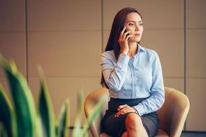 serieuze vrouw praten over de telefoon in de lobby van het kantoor foto