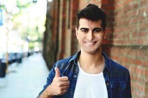 jonge man die lacht met duimen omhoog. buitenshuis foto