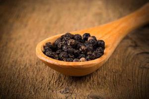 zwarte peper op houten lepel foto