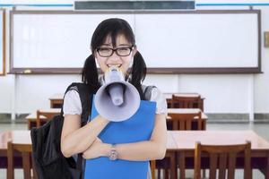 middelbare schoolstudent met megafoon in de klas foto