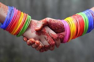 handen schudden versierd met kleurrijke armbanden foto