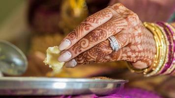 handen van de Indiase bruid eten foto