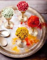 diverse indiaanse kruiden in vintage metalen bekers foto