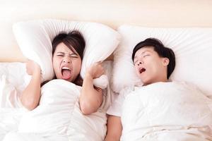 jonge vrouw verstoord door het gesnurk van haar man