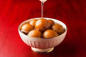 gulab jamun / indian snoepjes in een ronde keramische kom, foto