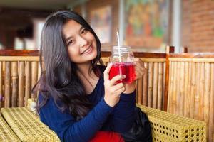 gelukkig meisje glimlachend bieden vers drankje in café foto
