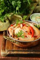 gebakken garnalen met chili in een koperen pan, indische stijl foto