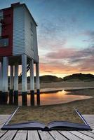 prachtige landschap zonsopgang stelten vuurtoren op conceptuele strand foto