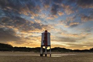 prachtige landschap zonsopgang paal vuurtoren op het strand foto