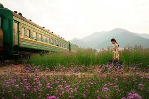 jonge vrouw met bagage in oude retro vintage trein foto