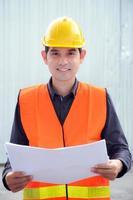 Aziatische ingenieur of voorman met veiligheidsvest en helm foto