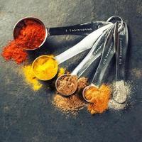 kleurrijke kruiden in metalen lepels foto