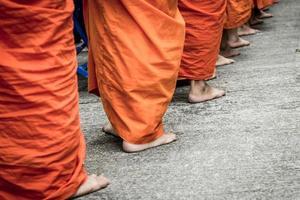 blootsvoets van boeddhistische monnik terwijl je op een rij staat foto