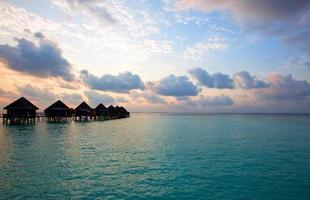 villa op palen in water bij zonsondergang tijd. foto