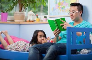 Aziatische vader en zijn dochter lezen