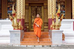 jonge boeddhistische monnik wandelen voor klooster foto