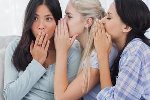 twee vrienden fluisteren geheimen aan geschokte brunette foto