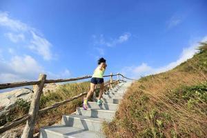 jonge fitness vrouw trail runner aangelopen op bergtrappen foto