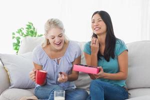 vrienden die een doos chocolaatjes delen en lachen foto