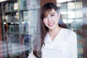 Aziatische mooie vrouwelijke student met boek in bibliotheek portret