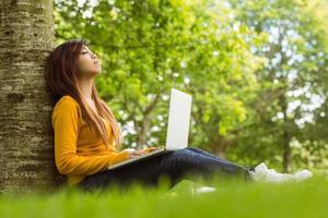 ontspannen vrouw met laptop in park foto