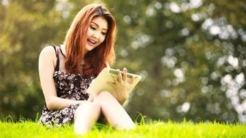 Aziatische vrouw die digitale tablet in park gebruiken foto