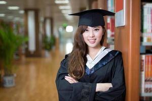 Aziatische mooie vrouwelijke student die academische kleding in bibliotheek draagt