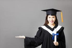 mooie jonge afgestudeerde bedrijf diploma met gebaar tonen foto