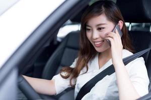 Aziatische mooie vrouw met behulp van mobiele telefoon en auto rijden foto