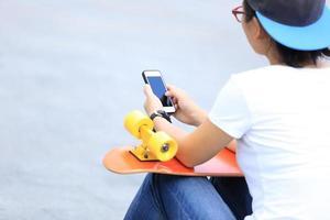 jonge skateboarder gebruiken mobiele telefoon zitten op trappen van de stad foto