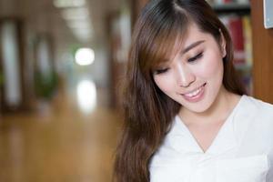 mooie Aziatische vrouwelijke student leesboek in bibliotheek