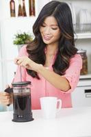 Aziatisch Chinees vrouwenmeisje dat in keuken koffie maakt foto