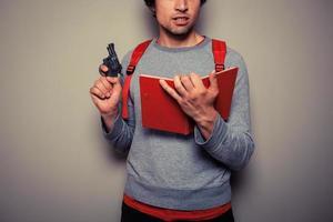 student met pistool en boek foto