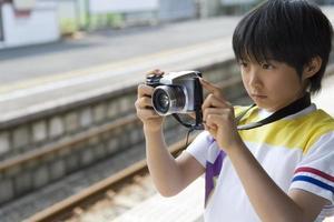 jongen bedrijf camera op het platform foto