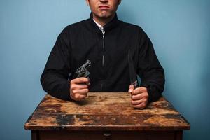 misdadiger aan tafel met pistool en mes foto
