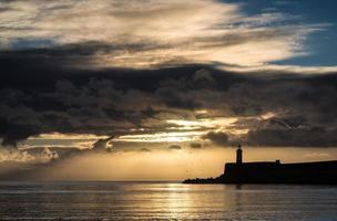 zonsopganghemel over kalme wateroceaan met vuurtoren en haven