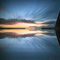 zonsopganghemel over kalme wateroceaan met vuurtoren en haven foto