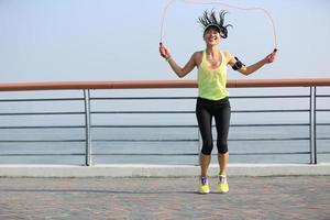 jonge fitness vrouw springtouw aan zee foto