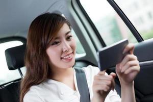 mooie Aziatische jonge vrouw met behulp van mobiele telefoon in de auto foto