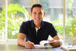 glimlachende man met boek geopend op tafel foto
