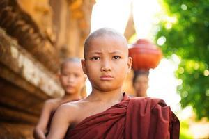 jonge boeddhistische monniken die ochtend aalmoes lopen foto