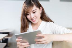 Aziatische mooie vrouwelijke studentenstudie met tablet in klaslokaal