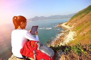 wandelende vrouw gebruik tablet pc aan zee foto