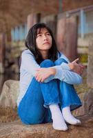 triest tiener meisje, zittend op de rotsen langs het meer, eenzame uitdrukking foto