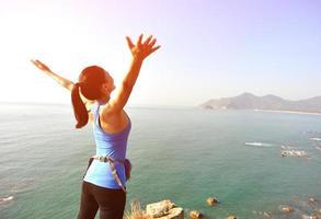 wandelende vrouw opgeheven armen naar de blauwe zee foto