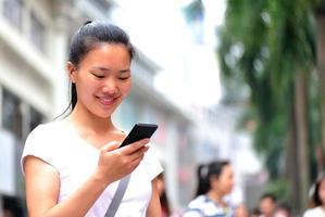vrouw met behulp van haar mobiele telefoon op straat foto