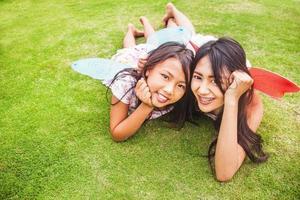 twee Indonesische zussen liggend op een gras foto