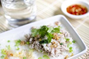 zacht gekookt rijstvarkensvlees met glas water en vissaus foto
